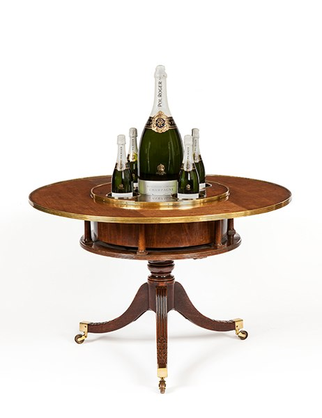 Based on a 1793 design by George Hepplewhite, the great English cabinetmaker, this extraordinary circa-1800 mahogany gentleman's social table is 28.5 inches tall and 42.25 inches in diameter, features gleaming brass banding, and banded with gleaming brass, and holds decanters or bottles of wine in metal sleeves. The central well—shown filled with a giant bottle of Pol Roger—is actually an ice bucket. The Marquess of Salisbury owns a similar historic table, which is displayed in a dining room at Hatfield House, though typically it would have been used for after-dinner imbibing. Apter-Fredericks is offering the antique for $150,000.